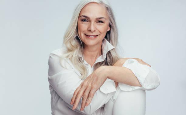 vacker mogen kvinna sitter över vit bakgrund - mature women studio grey hair bildbanksfoton och bilder
