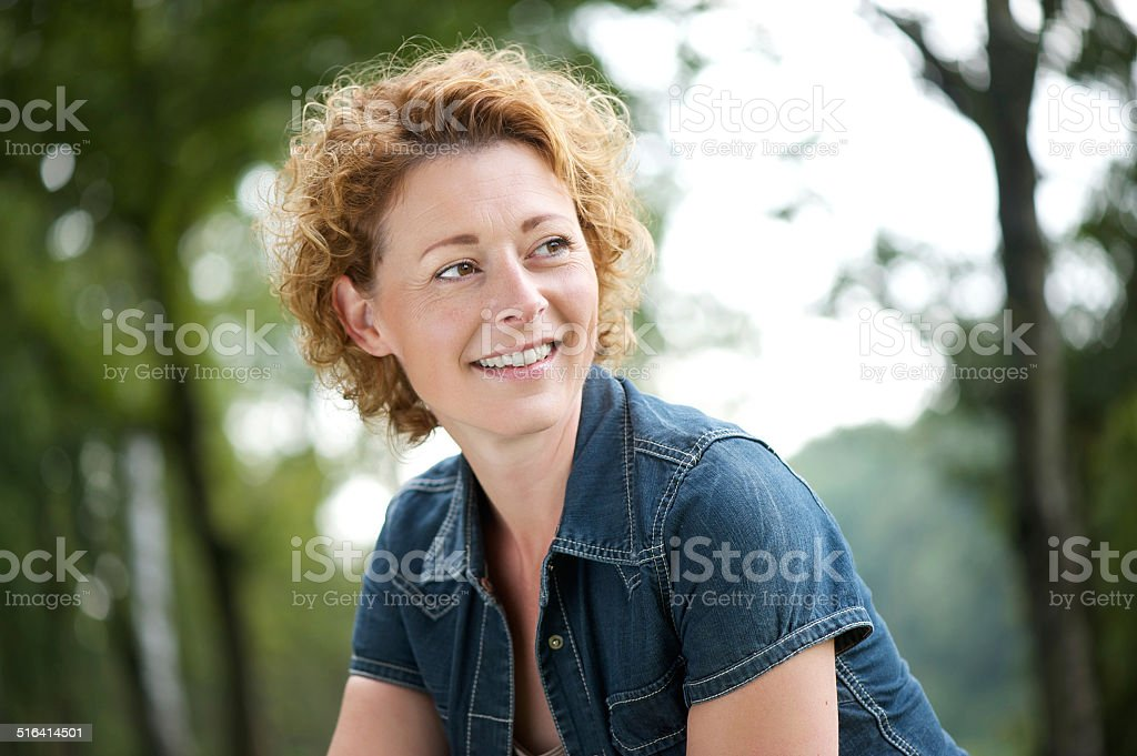 Beautiful mature woman smiling and looking away stock photo
