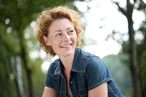 bella donna matura sorridente e guardando lontano - woman portrait forest foto e immagini stock