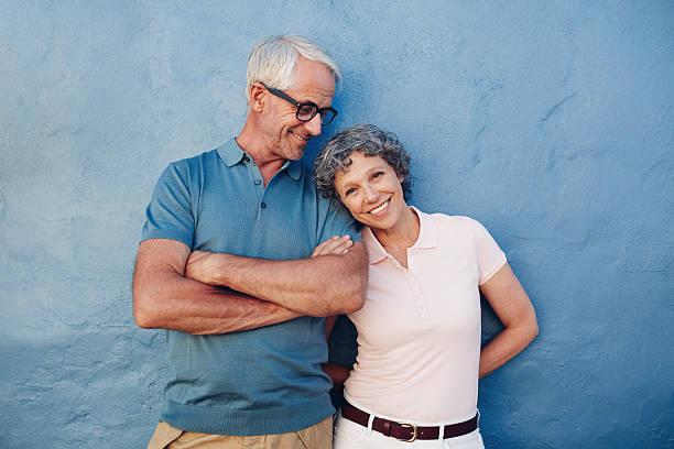 beautiful mature woman standing with her husband - mid volwassen stockfoto's en -beelden