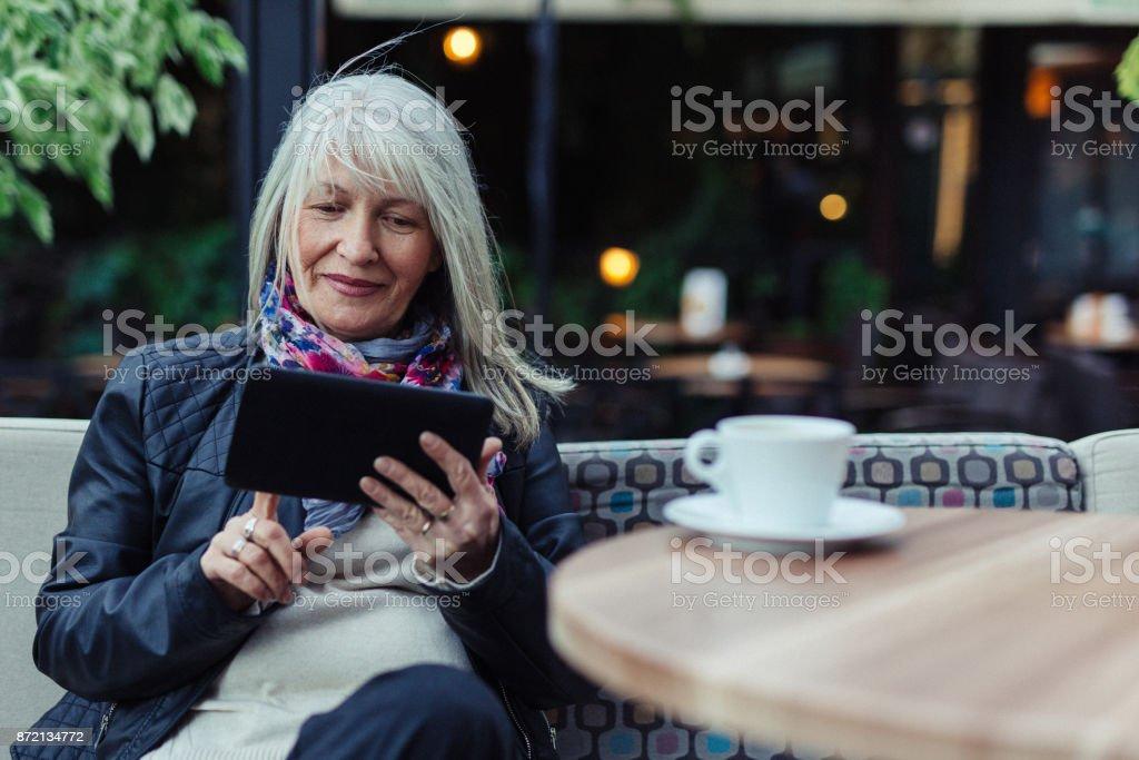 Beautiful mature woman using technology in cafe stock photo