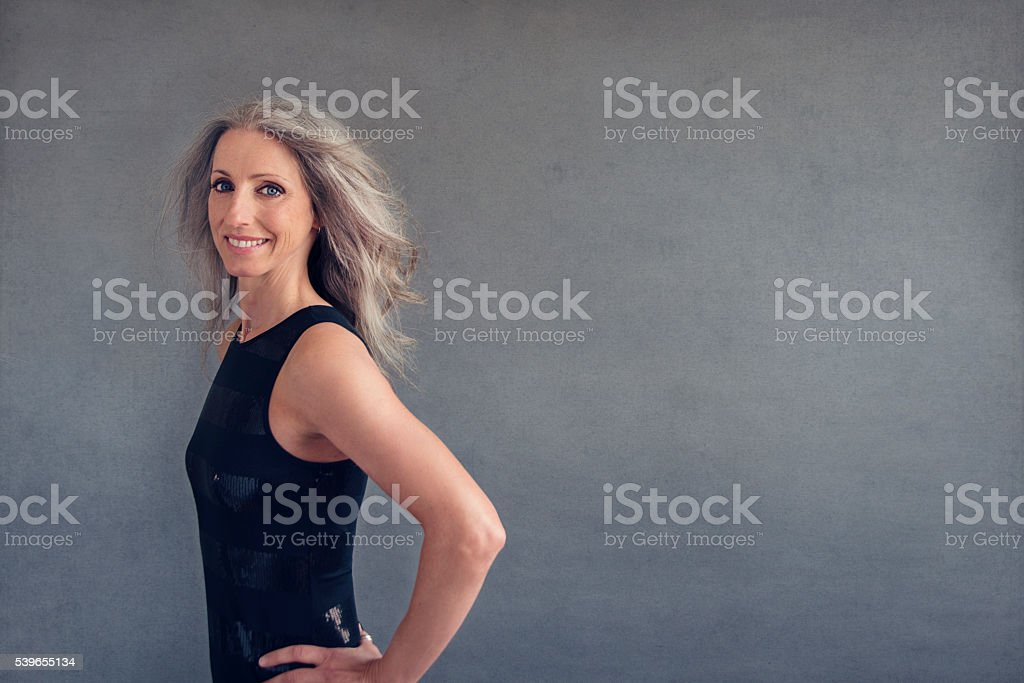 Beautiful mature woman with silver hair and black long dress. stock photo