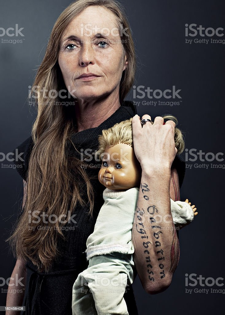 beautiful mature woman with tattoos and a doll indoor royalty-free stock photo