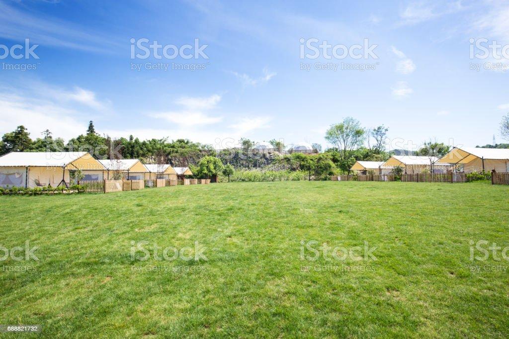 beautiful meadow near village in blue sky stock photo