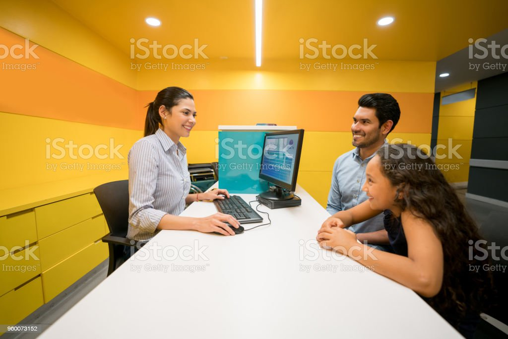 Beautiful medical assistant opening medical chart for a pediatric patient and father sitting next to his daughter all smiling stock photo