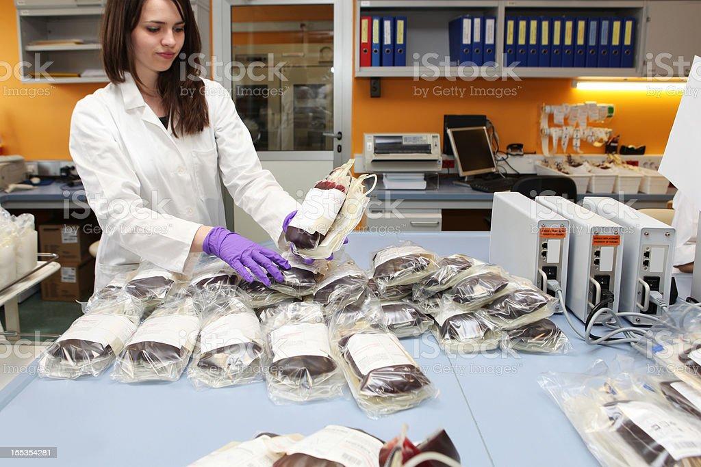 Linda médica Trabalhador em um sangue bank.pile de bloodbags - foto de acervo