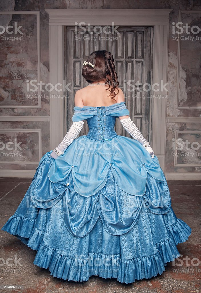 Beautiful medieval woman in blue dress, back stock photo