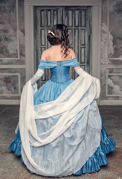 wunderschöne mittelalterliche frau im blauen kleid, die auf der rückseite - prinzessinnenstil stock-fotos und bilder