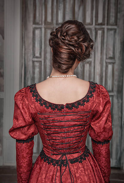Beautiful medieval woman in red dress, back stock photo