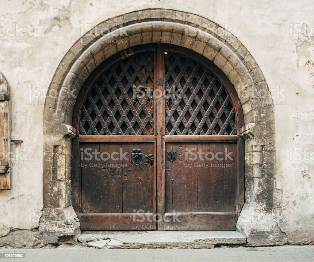 Beautiful medieval wooden gate with stone arch in old weathered building stock photo