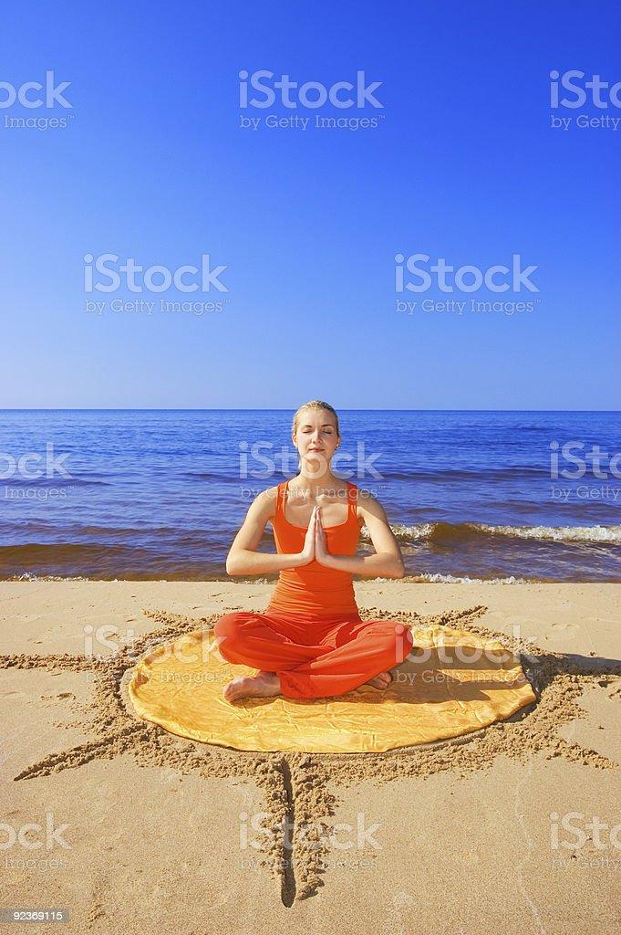Beautiful meditating girl on the beach royalty-free stock photo