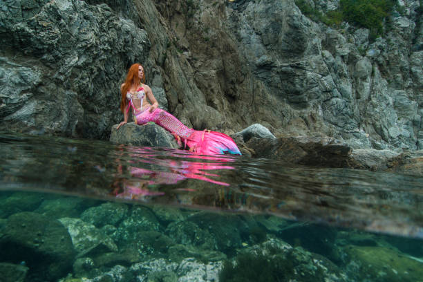 schöne meerjungfrau mit long-tail am meeresufer - meerjungfrau wellen stock-fotos und bilder