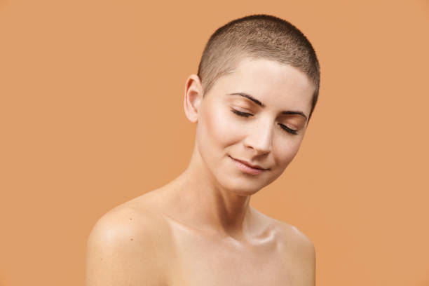 Beautiful mid 30s woman with closed eyes and peaceful facial expression. Photo of attractive caucasian woman with perfect skin on beige background. Youth and Beauty concept. Beautiful mid 30s woman with closed eyes and peaceful facial expression. Photo of attractive caucasian woman with perfect skin on beige background. Youth and Beauty concept. shaved head stock pictures, royalty-free photos & images
