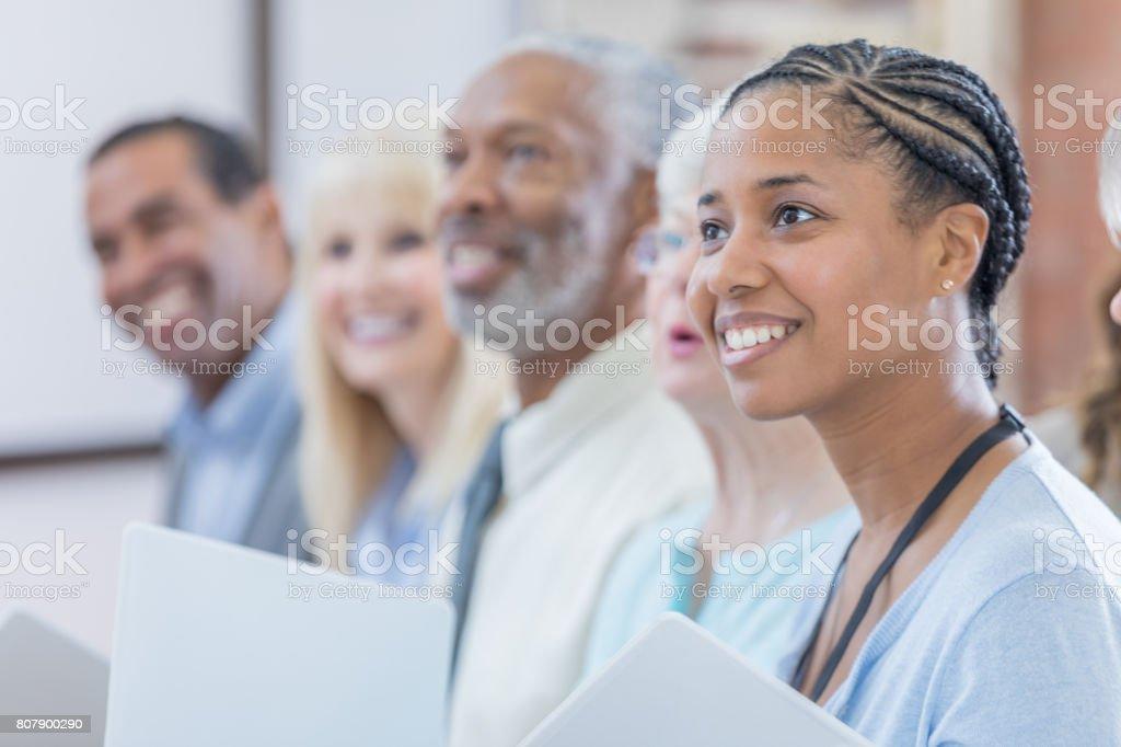 Vackra mitten av vuxen kvinna deltar i fortbildning klass bildbanksfoto
