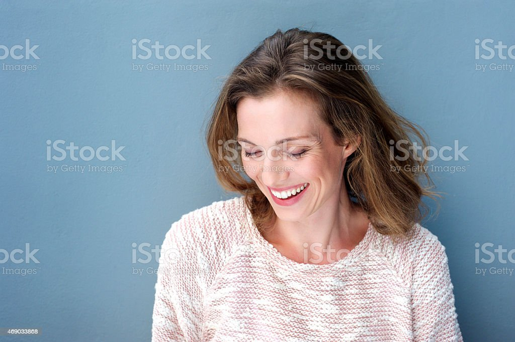 Beautiful mid adult woman laughing with sweater stock photo