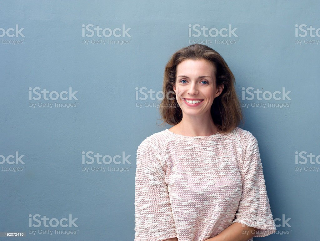 Beautiful mid adult woman smiling on gray background stock photo