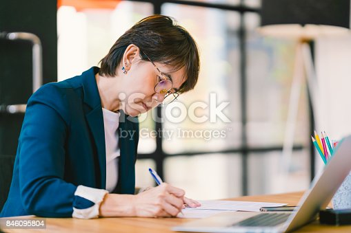 istock Beautiful middle age Asian woman working on paperwork in modern contemporary office, with laptop computer. Business owner, entrepreneur, executive manager, or employee office worker concept 846095804