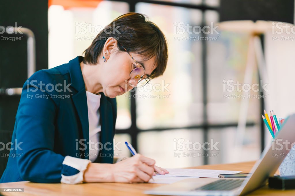Beautiful middle age Asian woman working on paperwork in modern contemporary office, with laptop computer. Business owner, entrepreneur, executive manager, or employee office worker concept stock photo