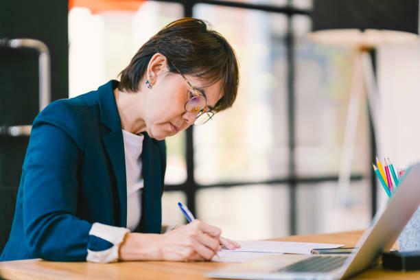 美しい中年のアジアの女性でラップトップ コンピューター、モダンな現代的なオフィスの書類事務に取り組んでいます。ビジネスの所有者、起業家、エグゼクティブ マネージャー、または従業員のオフィス ワーカーの概念 ストックフォト