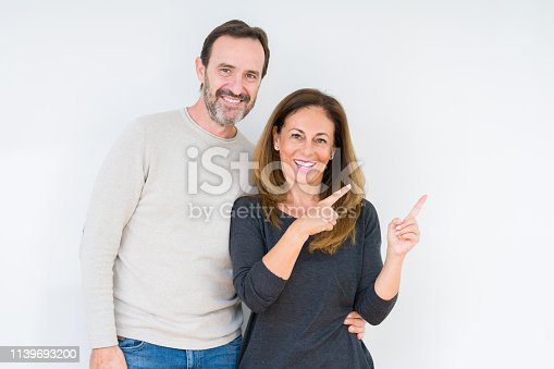 istock Beautiful middle age couple in love over isolated background smiling and looking at the camera pointing with two hands and fingers to the side. 1139693200