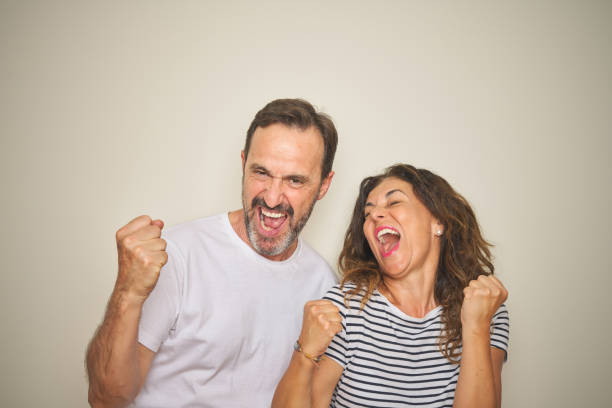 beautiful middle age couple together standing over isolated white background very happy and excited doing winner gesture with arms raised, smiling and screaming for success. celebration concept. - sud europeo foto e immagini stock
