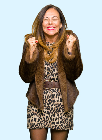 istock Beautiful middle age elegant woman wearing mink coat excited for success with arms raised celebrating victory smiling. Winner concept. 1097864824
