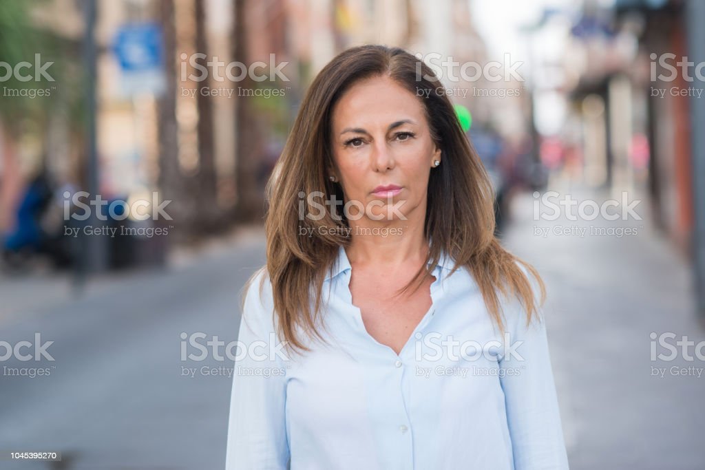 Beautiful middle age hispanic woman at the city street on a sunny day...