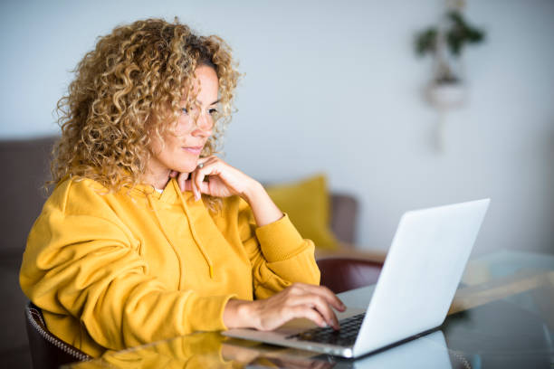 Beautiful middle age modern woman work at computer laptop at home sitting at the table - digital smart work concept with internet technology and alternative office - job search concept stock photo