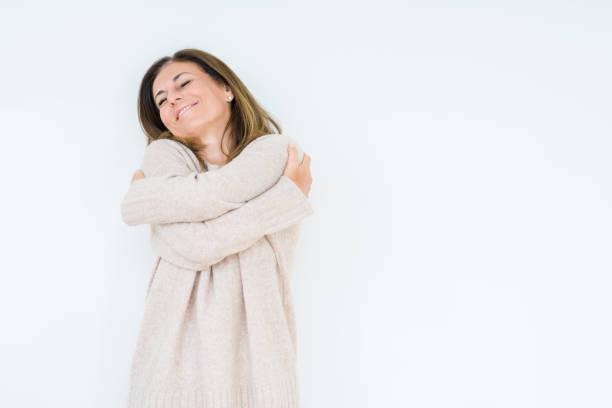 beau moyen age femme sur isolé fond étreindre soi heureux et positif, le sourire confiant. l'amour de soi et d'autogestion de la santé - femme seule s'enlacer photos et images de collection