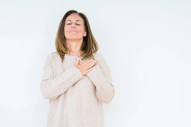 schöne mittelalterfrau über isolierten hintergrund lächelnd mit händen auf der brust mit geschlossenen augen und dankbarer geste im gesicht. gesundheitskonzept. - die wahrheit tut weh stock-fotos und bilder