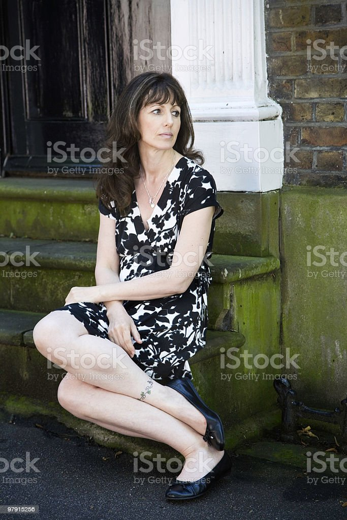 Beautiful middle age woman sitting on the steps, waiting royalty-free stock photo