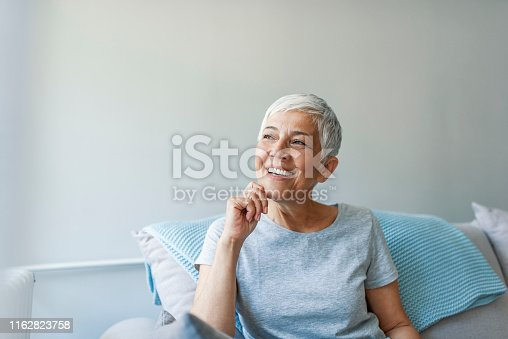 istock Beautiful middle age woman smiling at home 1162823758