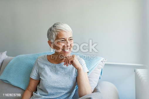 istock Beautiful middle age woman smiling at home 1162823759