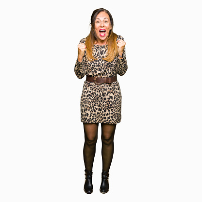 istock Beautiful middle age woman wearing leopard animal print dress celebrating surprised and amazed for success with arms raised and open eyes. Winner concept. 1097877324