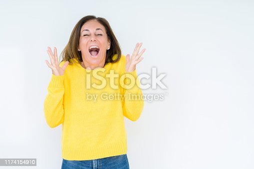587932042istockphoto Beautiful middle age woman wearing yellow sweater over isolated background celebrating mad and crazy for success with arms raised and closed eyes screaming excited. Winner concept 1174154910