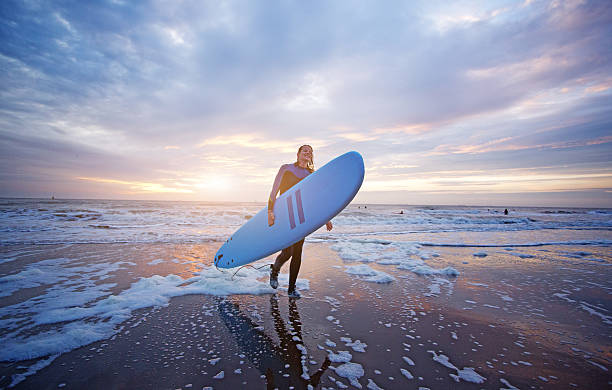 Beautiful middle aged female surfer on beach at dusk Beautiful middle aged female surfer on beach at dusk wetsuit stock pictures, royalty-free photos & images