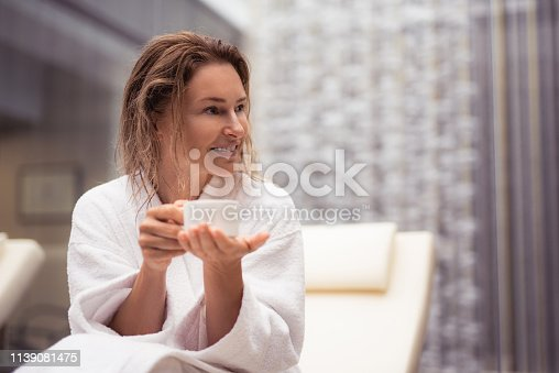 I see something interesting. Waist up portrait of beautiful woman with coffee sitting on daybed at spa lounge. She is looking away with smile