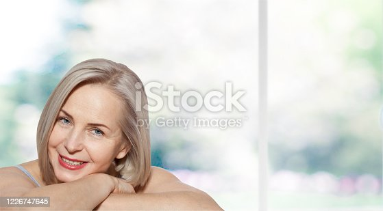 Beautiful middle aged woman fase close up on grey background