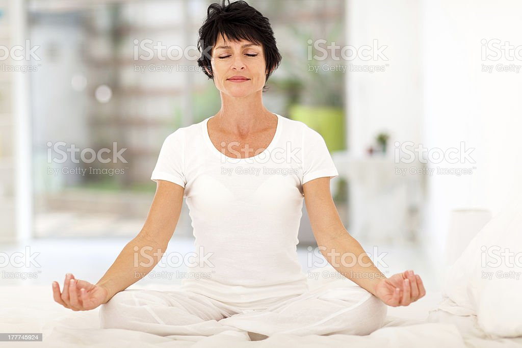 beautiful middle aged woman meditation on bed royalty-free stock photo