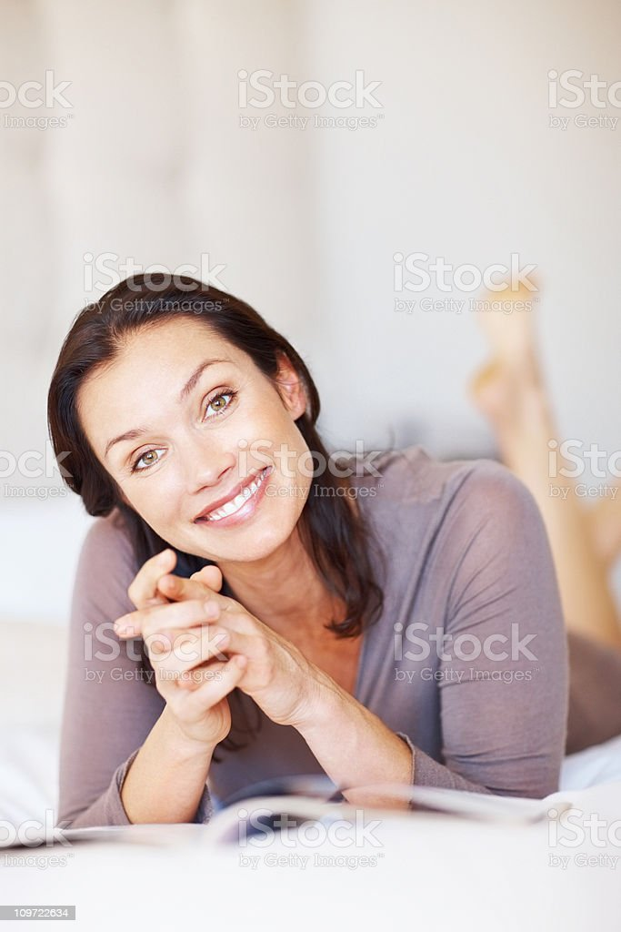 Beautiful middle aged woman smiling while lying on bed royalty-free stock photo