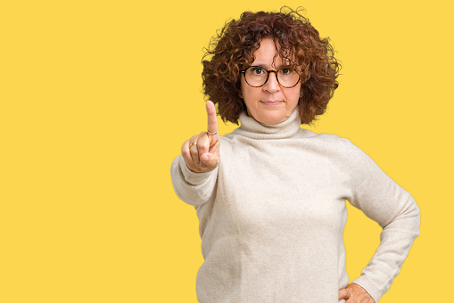 Beautiful middle ager senior woman wearing turtleneck sweater and glasses over isolated background Pointing with finger up and angry expression