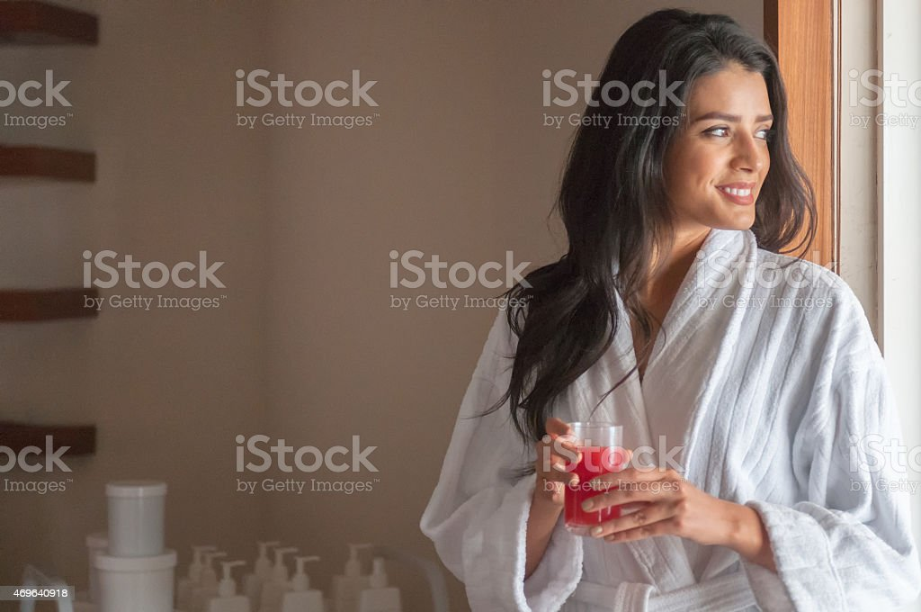 Beautiful Middle Eastern Woman Relaxing in Spa with Fresh Juice stock photo