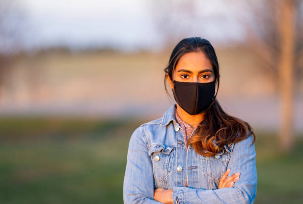 Beautiful Middle Eastern Women Wearing Protective Mask Outside During Sunset stock photo
