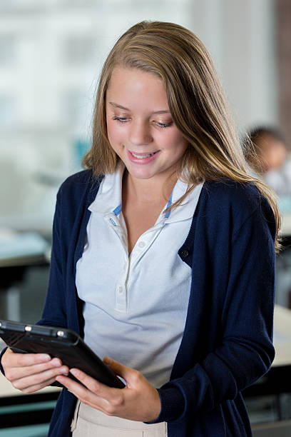 Beautiful middle school student reads something on tablet Pretty Caucasian middle school student looks at something on her digital tablet. She is standing in her classroom. She is wearing a navy sweater with white blouse underneath. Her classmates are working in the background. cute middle school girls stock pictures, royalty-free photos & images