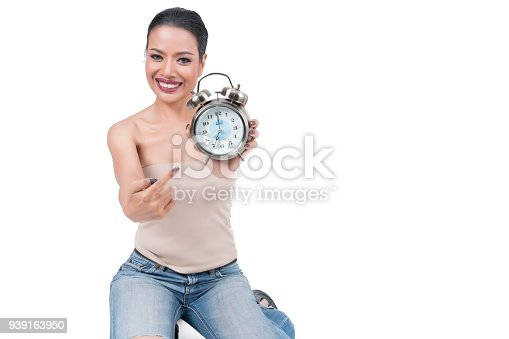 istock Beautiful middle-aged Asian woman smiling and pointing finger at  alarm clock isolated on white background 939163950