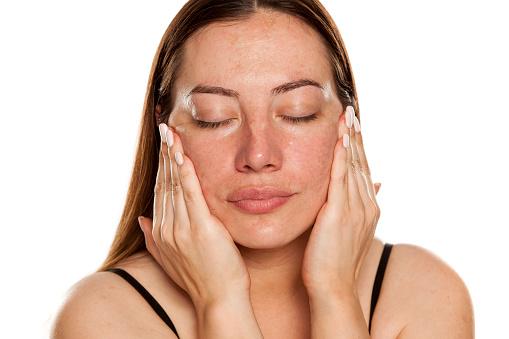 美麗的中年婦女應用潤膚霜在她的臉上白色背景 照片檔及更多 一個人 照片