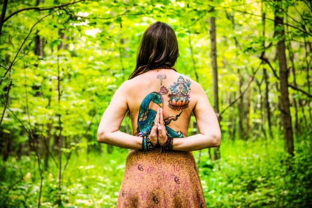 schöne, mittleren alters frau praktizieren yoga außerhalb in einem wald - danke an lehrerin stock-fotos und bilder
