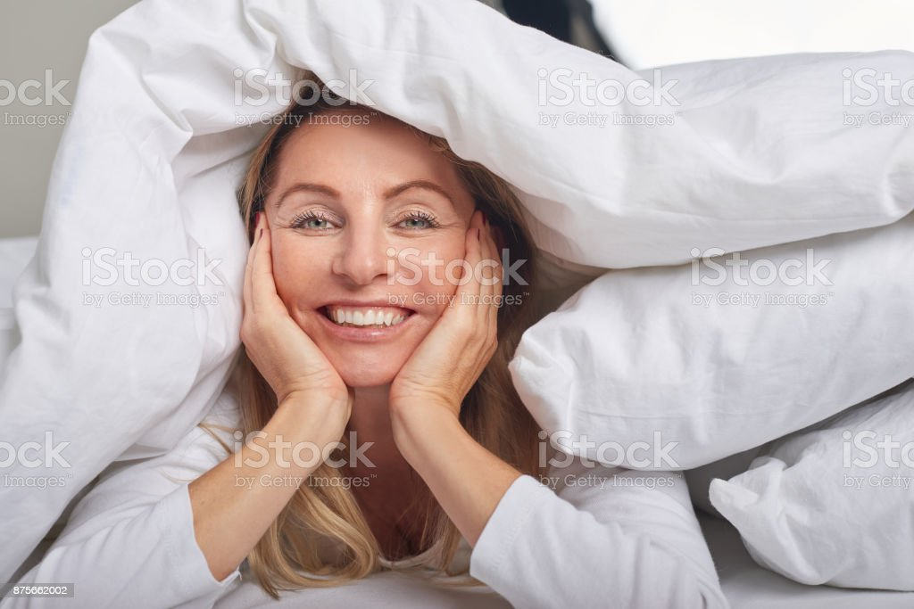 Beautiful middle-aged woman under sheets stock photo