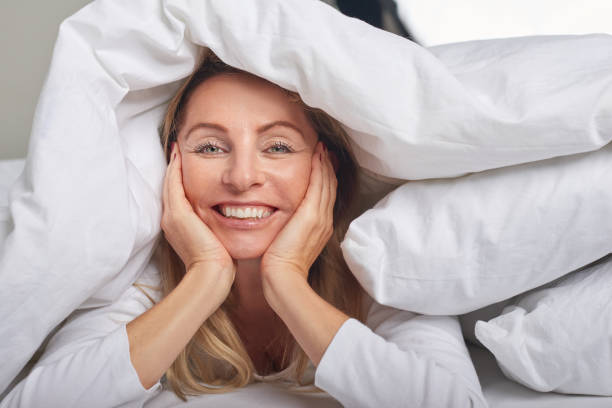 Beautiful middle-aged woman under sheets Beautiful middle-aged woman under white sheets looking at camera with a happy smile duvet stock pictures, royalty-free photos & images