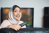 A pretty young Muslim woman holding a TV remote control turns to camera and laughs.